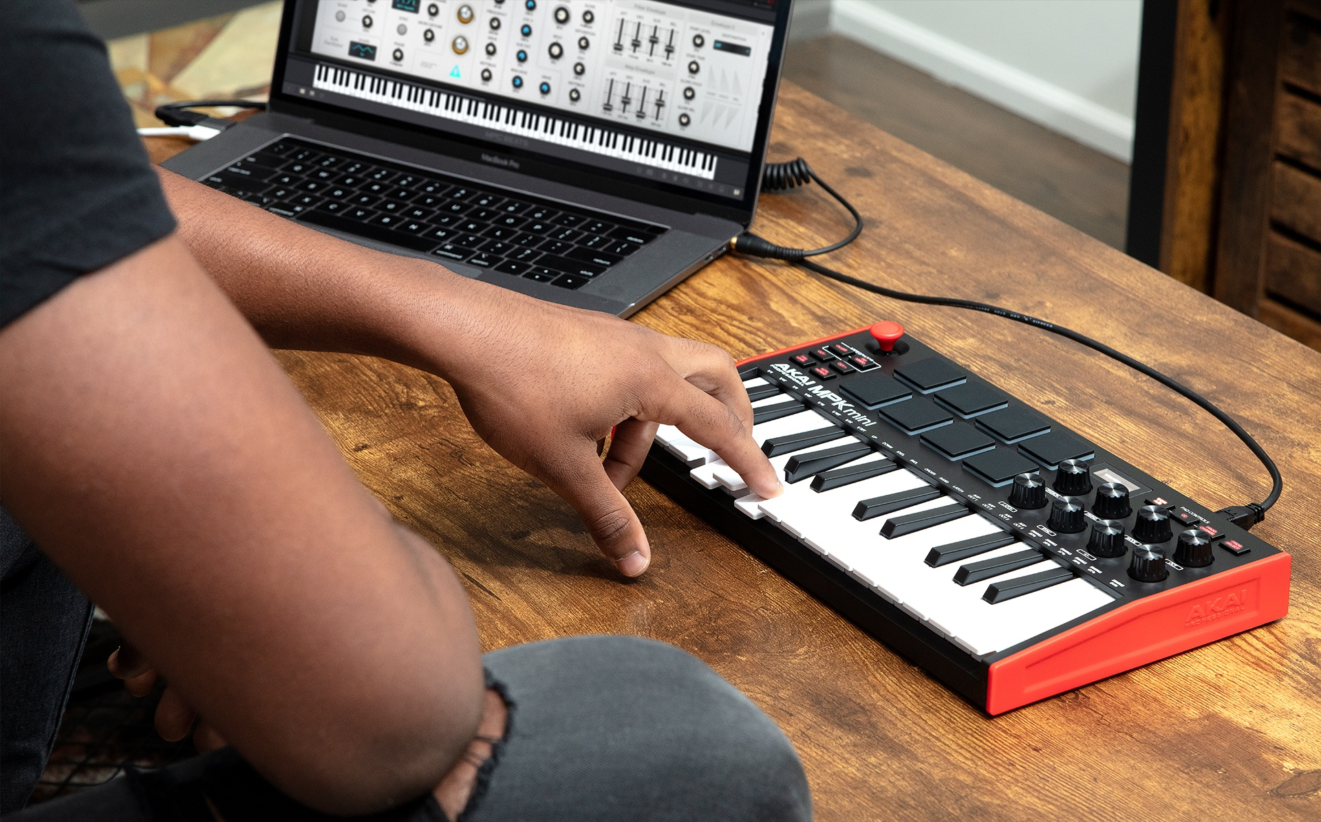 Music producer playing MPK Mini keys on laptop with MPC Beats